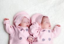 Newborn twins sisters sleeping on white fur, wearing pink sweaters